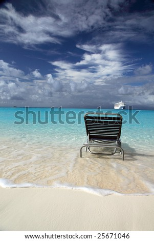 Cruise ship and lounging chair on tropical island beach resort