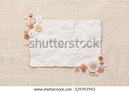 Crumpled paper decorated with white and pink buttons