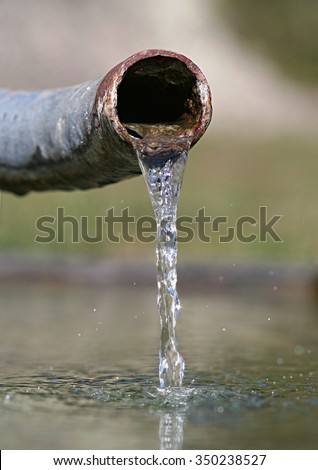 Crystal clear fresh water emerging from a rusty pipe. Conceptual image illustrating water scarcity and the importance of fresh clean water in the environment.