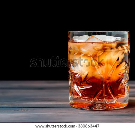 crystal glass of whiskey with ice on a wooden table on a dark background