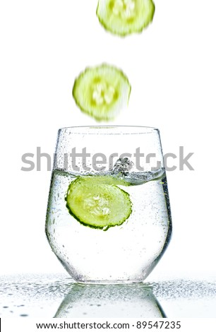 cucumber falling into glass of water