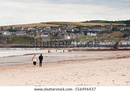 Cullen Bay, Scotland - August 14th 2016: elderly couple walking along a deserted  Cullen beach in Morayshire, Scotland on a particularly cold and windy summer day