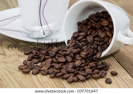 Cup filled with Coffee Beans on wooden background