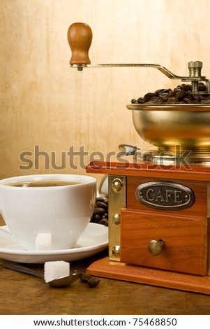 cup full of coffee, beans, pot and grinder on wood