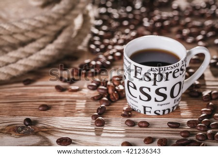 Cup of black coffee in cup on wooden table next coffee beans and rope.