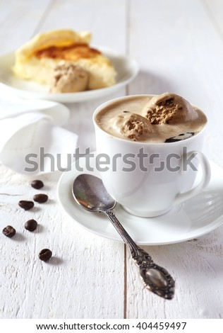 Cup of black coffee with ice cream and cheesecake