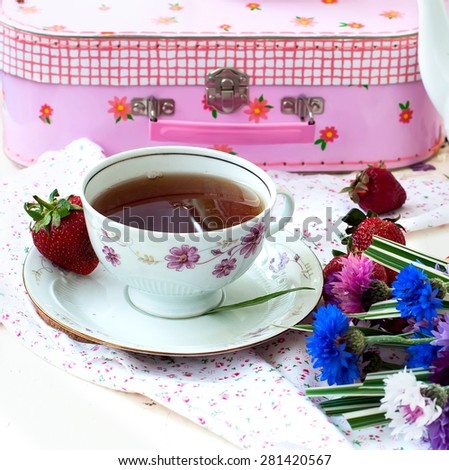 cup of black tea, strawberries and a bouquet of multi-colored cornflowers. serving breakfast