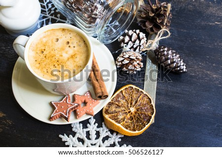 Cup of cappuccino with cinnamon spice and Christmas decoration on dark rustic background