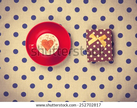 Cup of Cappuccino with heart shape symbol and gift box on polka dot background.