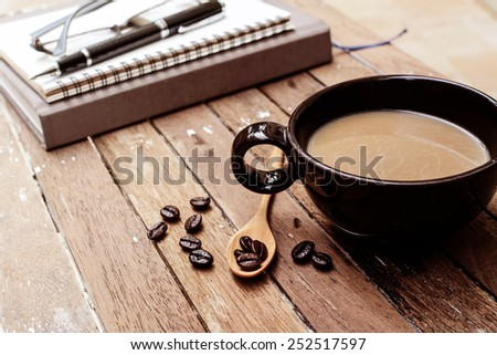 Cup of coffee and beans with notebook, soft light filter, Vintage style