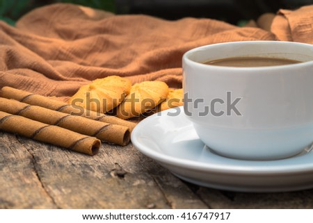 Cup of coffee and cookies on old wooden background