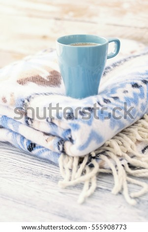 Cup of coffee and cozy plaid with blue winter pattern