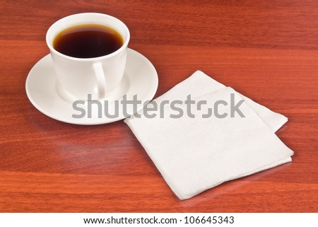Cup of coffee and napkin on table