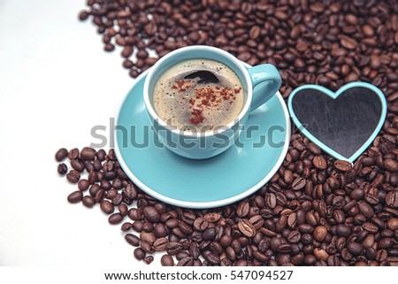 Cup of coffee, coffee beans and decorative item in the shape of heart on white background.