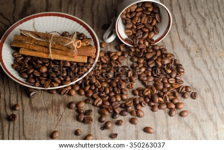 cup of coffee on vintage cinnamon coffee beans on a wooden table,horizontal photo