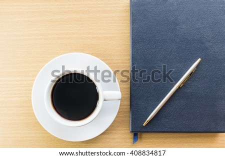 Cup of coffee on wood deck and notebook