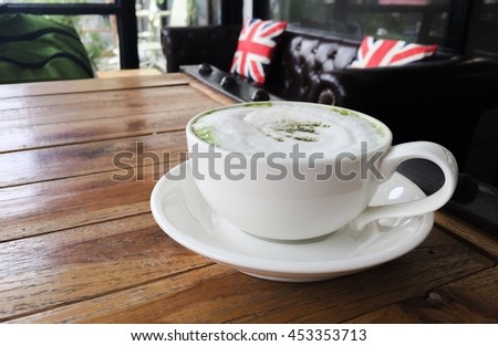 Cup of coffee on wooden table with blur sofa in coffee shop background. soft focus. filter effect.