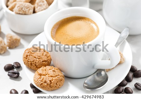 cup of espresso and cookies on a white table, closeup, horizontal