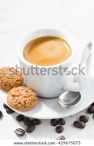 cup of espresso and cookies on table, vertical