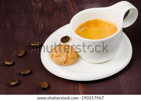 cup of espresso coffee and biscuit near coffee beans on old wood
