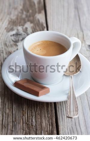 Cup of fresh brewed espresso and milk chocolate on wooden table
