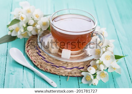 Cup of fresh herbal tea with jasmine on  wooden background. Selective focus, horizontal.
