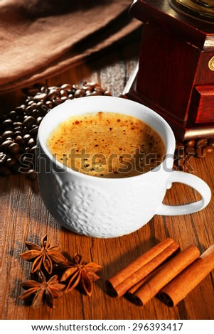 Cup of fresh spicy coffee with beans on table, closeup