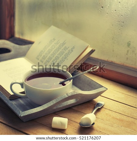 Cup of hot tea and book on a wooden tray