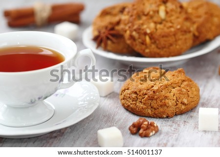 Cup of hot tea and oatmeal cookies with nuts, raisins and cinnamon
