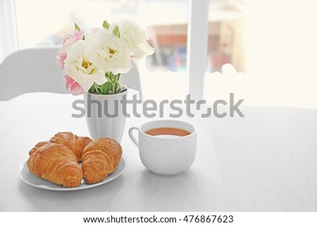 Cup of tea with flowers and croissants on table