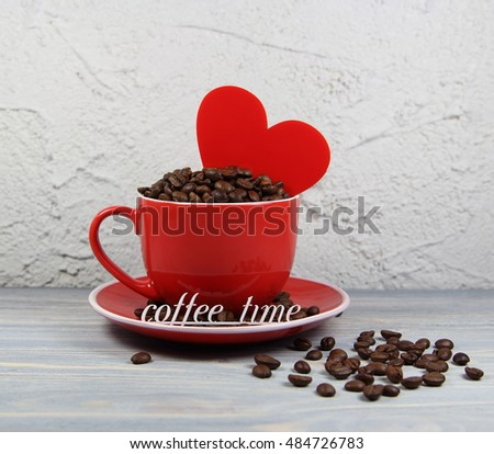 cup red with coffee grains, heart and an inscription coffee time