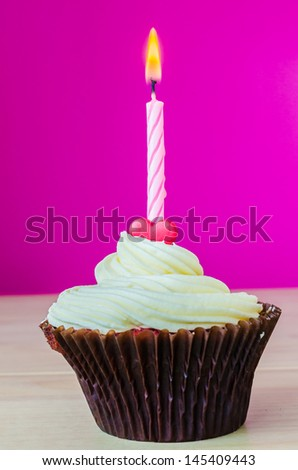 Cupcake with candle on color background
