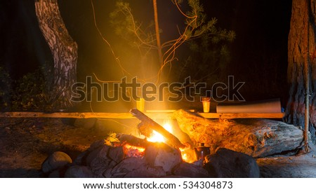Cups, backgammon and sleeping Mat lay on the bench from the Board at the tourist Park at night near a fire burning in the stones with sparks in the forest in the Altai.