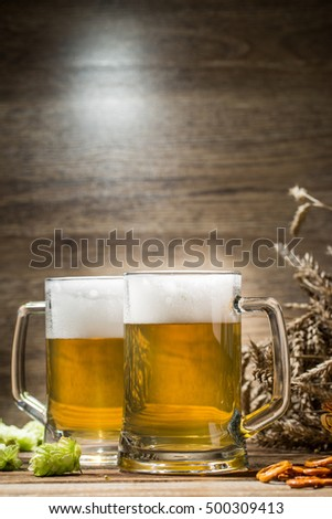 Cups with frothy beer on table in empty wooden background