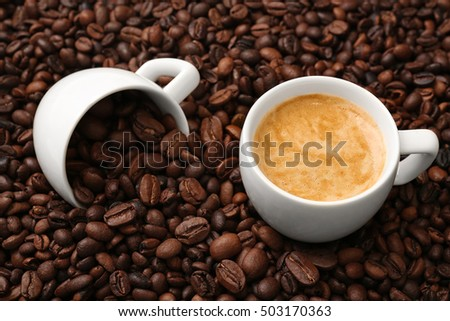 Cups with hot coffee and coffee beans, close up view