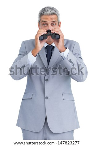 Curious businessman on white background observing with binoculars