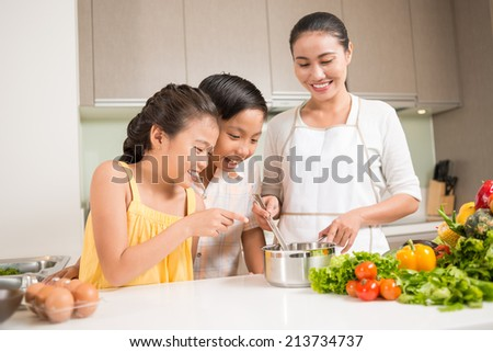Curious children looking into saucepan in hands of their mother