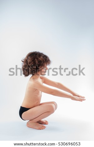 Curly boy in swimming trunks performing squat exercises. Blue background.