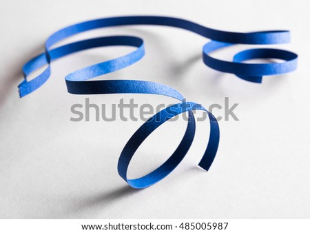 Curved blue paper ribbon on a white background. Macro lens closeup shot 1:1