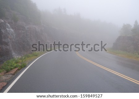Curving mountain top road in heavy fog on a mountain with pink granite sides of rocks
