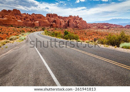Curvy road in a dry and desert area with scenic view of orange mesas