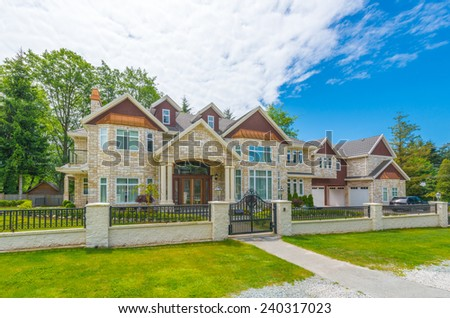 Custom built luxury house with nicely trimmed and landscaped front yard, lawn in a residential neighborhood. Vancouver, Canada.