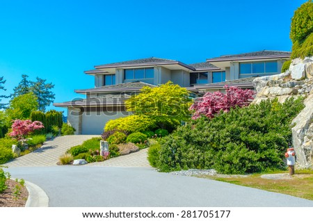 Custom built luxury house with nicely trimmed front yard, lawn and paved driveway to garage in a residential neighborhood. Vancouver Canada.