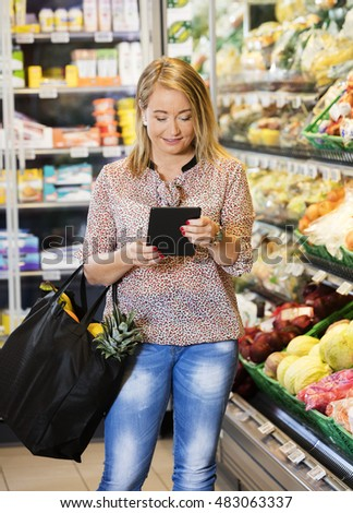 Customer Using Tablet Computer While Shopping In Grocery Store