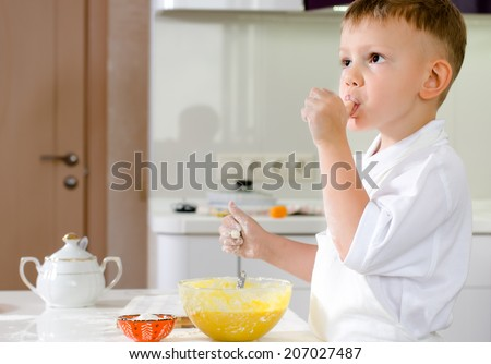 Cut little boy in a chefs uniform tasting his batter mixture sucking on his thumb as he checks the flavour and consistency