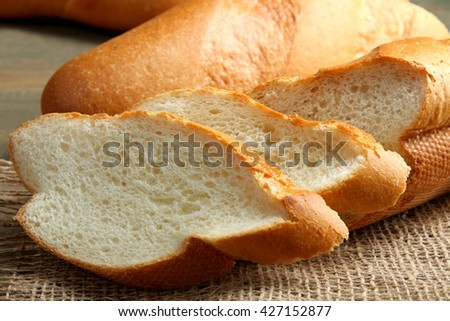 cut the baguette on sackcloth on wooden background