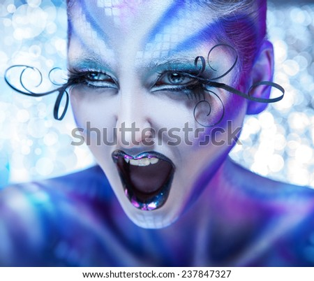 Cute and angry woman screaming. Creative make up on fashion model. Studio shot