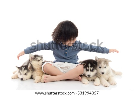 Cute asian boy sitting with siberian husky puppies on white background isolated