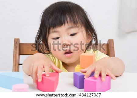 cute asian kid playing blocks
