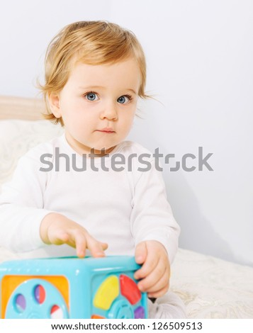 Cute baby boy playing indoors with toys